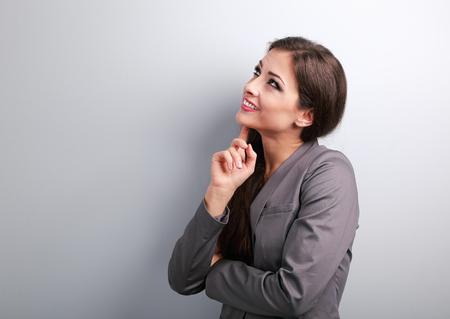 mujer pensando: Feliz pensamiento mujer de negocios y mirando hacia arriba sobre fondo azul Foto de archivo