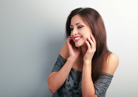 giggling: Happy laughing brunette young woman holding the hand at face and giggling on blue background