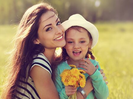 mother love: Beautiful smiling mother embracing her daughter with yellow bright flowers on summer background. Closeup portrait of family love in mother day