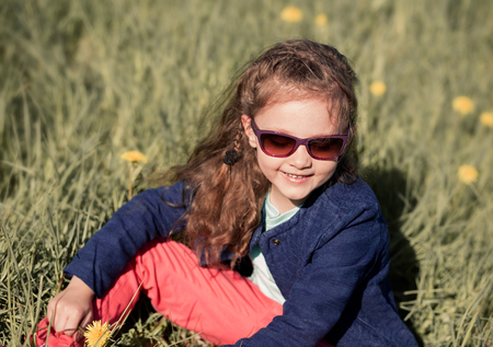 cute little girl: Fashion smiling kid girl sitting in green grass with flowers in fashion sunglasses and blue jacket Stock Photo
