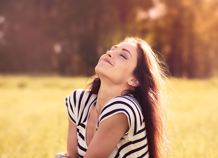 Beautiful relaxing woman sitting on the grass  and enjoying fresh air in sunny summer day on nature background