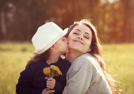 dar un regalo: hija feliz disfrutando de besar a su madre en el fondo de sol del verano