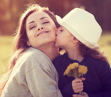 fille heureuse embrassant sa mère en profitant en été fond ensoleillé