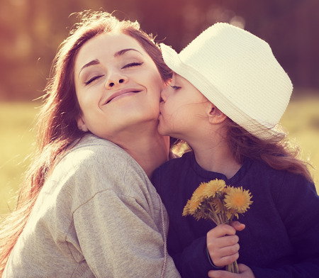Happy daughter kissing her enjoying mother on summer sunny background