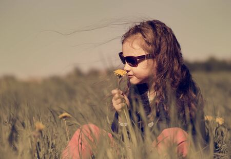 child model: Fashion kid girl sitting on the grass in sunglasses on summer background