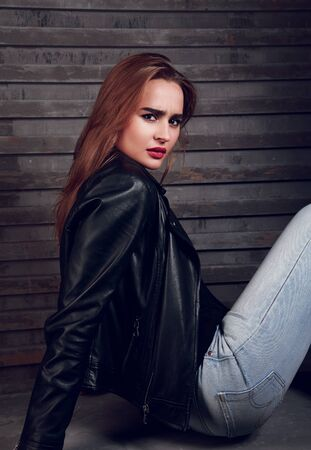 rocker girl: Serious red hair woman sitting in black jacket and blue jeans on street wall background Foto de archivo
