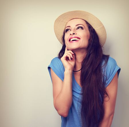 chuckle: Happy laughing excited woman in hat looking up on empty copy space. Vintage portrait