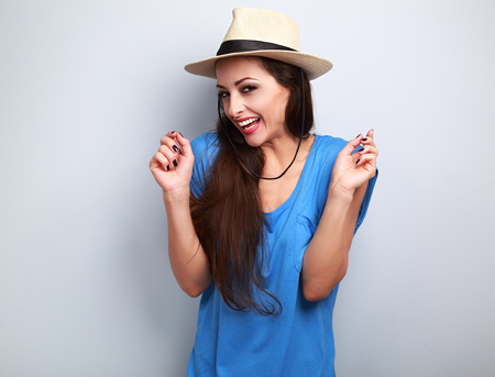 chuckle: Happy giggling young woman with straw hat on blue background looking in camera