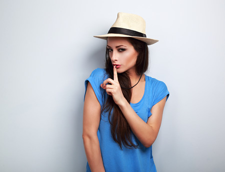 summer sign: Beautiful makeup female model in summer casual hat showing secret sign on blue background with empty copy space Stock Photo