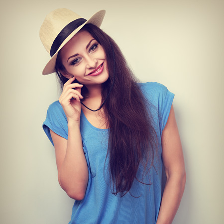 happy woman: Friendly casual woman in hat looking happy on blue background Stock Photo