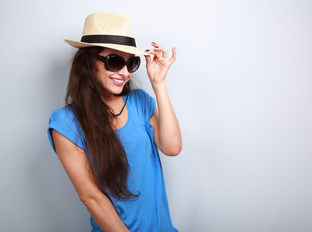 fashion clothes: Smiling beautiful young woman with straw hat and fashion sun glasses on blue background with empty copy space