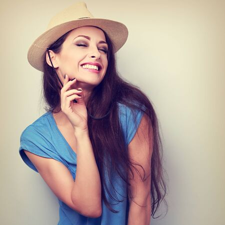 chuckle: Happy casual toothy laughing woman in summer hat. Vintage toned portrait