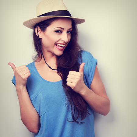 Optimistic casual woman in blue top and hat showing thumb up by two hands with happy emotion. Vintage toned portrait