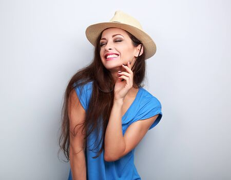 chuckle: Happy casual toothy laughing woman in summer hat on blue background Stock Photo