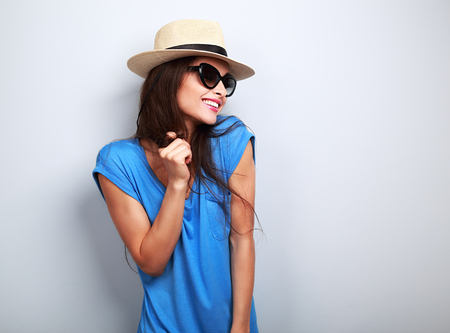 Happy enjoyment young woman in sun glasses and hat posing on blue background 版權商用圖片
