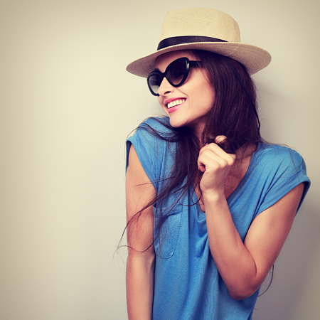 Happy enjoyment young woman in sun glasses and hat posing. Vintage toned portrait 版權商用圖片