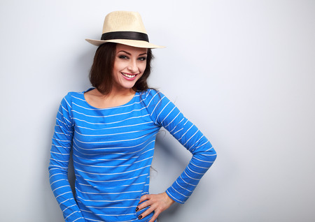Happy casual hipster young woman in straw hat looking on blue background