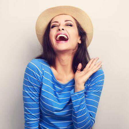 Rire jeune femme en chapeau de paille, les yeux fermés et la main près du visage. portrait agrandi Toned