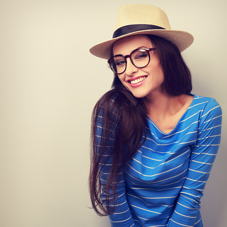 Happy young casual woman in eye glasses and straw hat looking with natural emotion. Toned bright portrait