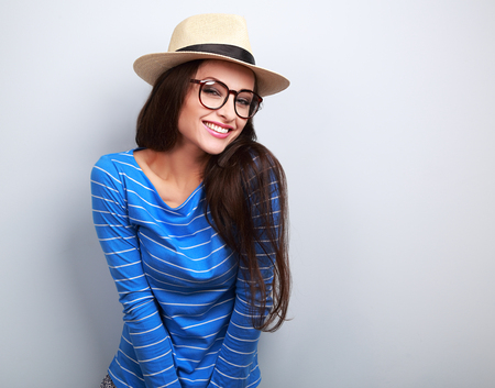 specs: Happy young casual woman in eye glasses and straw hat looking with natural emotion