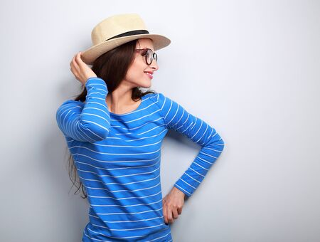 woman  glasses: Happy woman posing in profile in glasses and straw hat on blue background Stock Photo