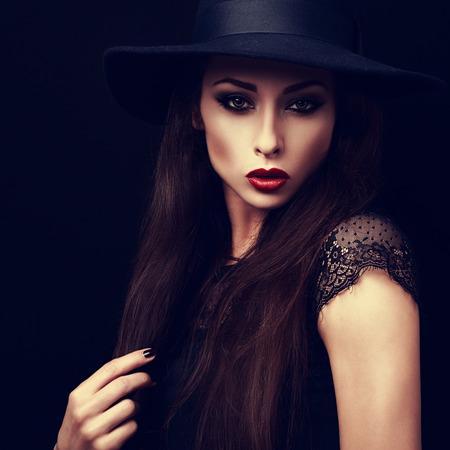 red lips: Maquillaje de la mujer misteriosa en el sombrero looking manera expresiva. lápiz de labios rojo brillante y maquillaje de la tarde. Primer plano el retrato del arte