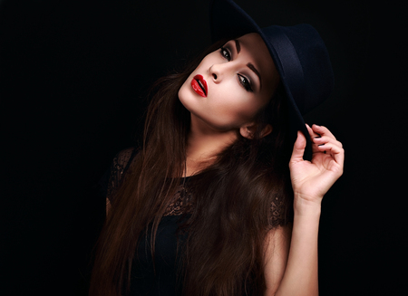 hot lips: Beautiful seductive bright makeup lady with red hot lips posing in hat on black background Stock Photo
