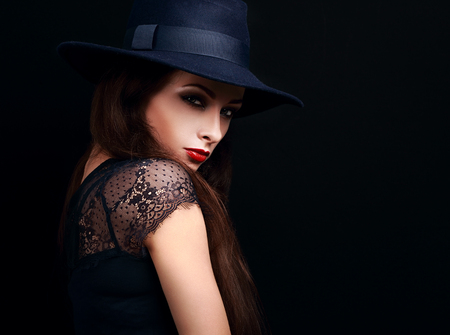 hot lips: Beautiful expressive bright makeup female model with red hot lips posing in hat on black background