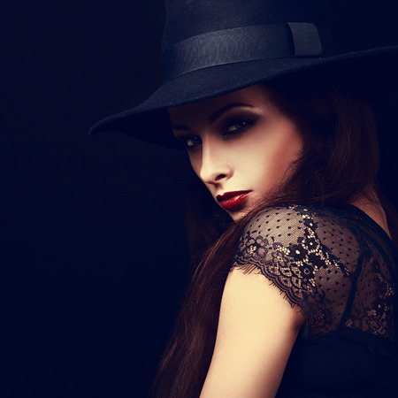 hot lips: Beautiful expressive bright makeup female model with red hot lips posing in hat. Halloween bright witch. Closeup Stock Photo