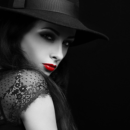 Beautiful expressive bright makeup female model with red hot lips posing in hat. Black and white portrait. Closeup Standard-Bild