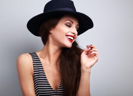 perfil de mujer rostro: con dientes de risa feliz del perfil de modelo femenino en negro elegante sombrero sobre fondo azul Foto de archivo