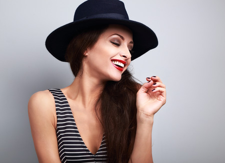 female model: Happy toothy laughing female model profile in black elegant hat on blue background Stock Photo