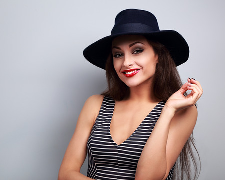 Happy smiling female model in black elegant hat looking on blue background Stock Photo