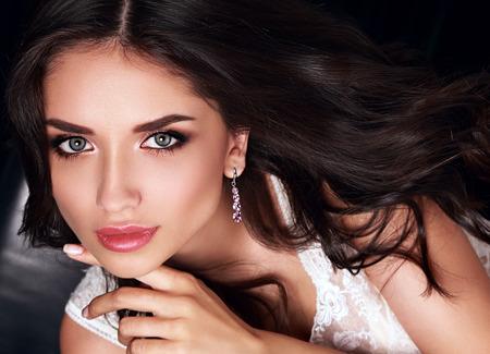 ピンクの口紅とファッション イヤリングでポーズをとって長い巻き毛の美しい化粧女性。ポートレート、クローズ アップ