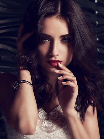 bangle: Sexy makeup female model with long curly hair touching dark red lips her manicured elegant finger. Toned closeup fashion portrait Stock Photo