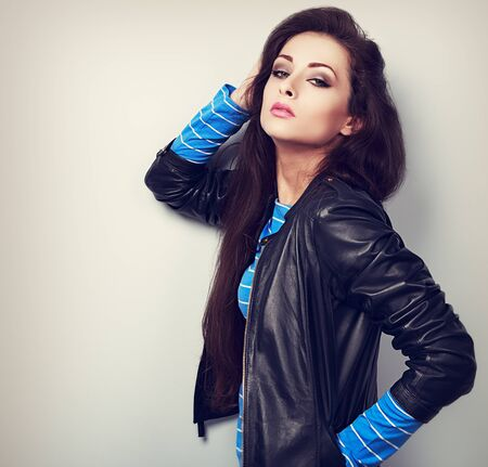 Sexy young woman posing in fashion black leather jacket. Toned closeup portrait