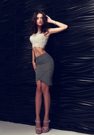 Beautiful female model posing in white top, fashion skirt and high heels near black stilish wall. Toned vertical portrait
