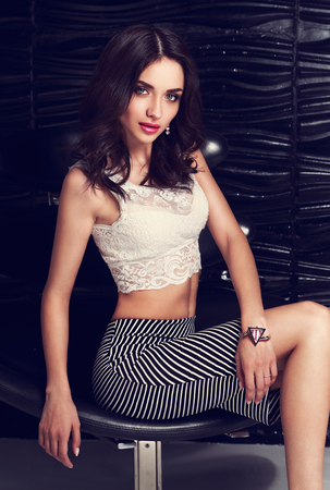 falda corta: Beautiful makeup woman sitting in armchair in white short top and skirt on black wall background. Bright closeup fashion portrait