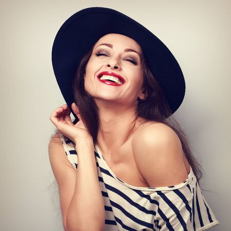 chuckle: Happy toothy laughing brunette young woman in black hat with closed eyes. Toned vintage portrait Stock Photo