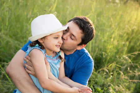 Happy father kissing her laughing daughter in hat on summer green grass background photo