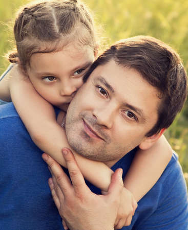 Happy kid girl hugging with love her smiling father on summer green grass background in sunny day. Closeup portrait of love photo