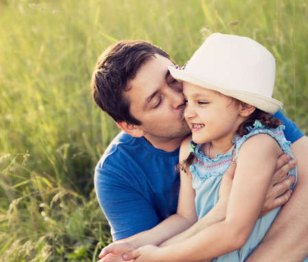 Happy father kissing her laughing daughter in hat on summer green grass background. Closeup portrait of love photo