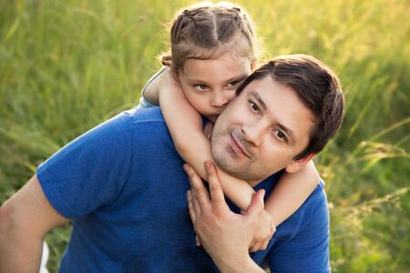 Happy kid girl hugging with love her smiling father on summer green grass background. Closeup portrait photo