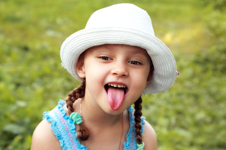 Fun kid girl in fashion hat showing the tongue with humor face on summer green grass background. Closeup portrait