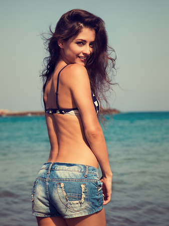 Beautiful happy woman in jeans shorts and bikini posing on blue sea and sky background. Vintage toned portrait