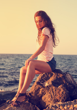 woman sunset: Beautiful thinking woman sitting on the stone on blue sea and sky background in sunset. Closeup portrait Stock Photo