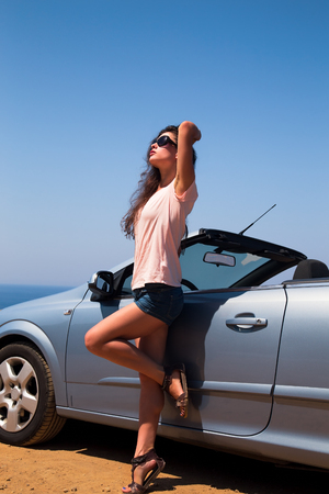 cabrio: Beautiful woman posing in short on blue sea and sky background near cabriolet car in sun glasses Stock Photo