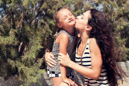 geen: Happy mother kissing her fun enjoying daughter on summer geen background