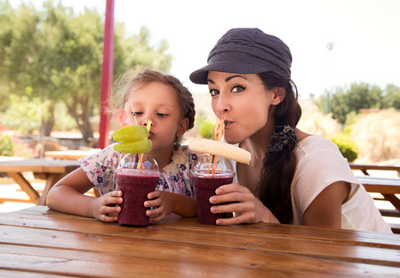 muchacha niño feliz y madre divertido emocional jugo de bayas de beber batido juntos en café de la calle