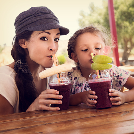 Happy kid girl and funny emotional mother drinking berries smoothie juice together in street cafe. Closeup portrait